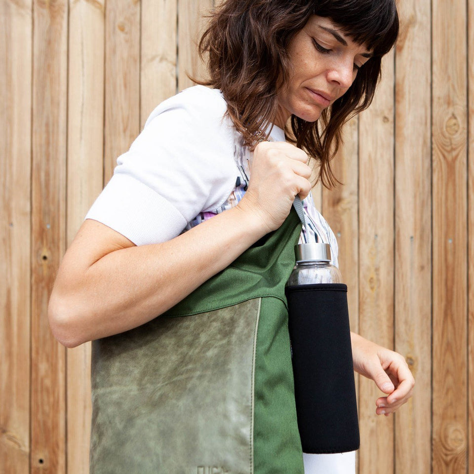 Dark haired woman with white t-shirt side detail view wearing the Muda leather bag green as a shoulder bag with a water bottle and a wooden tiles wall as the background