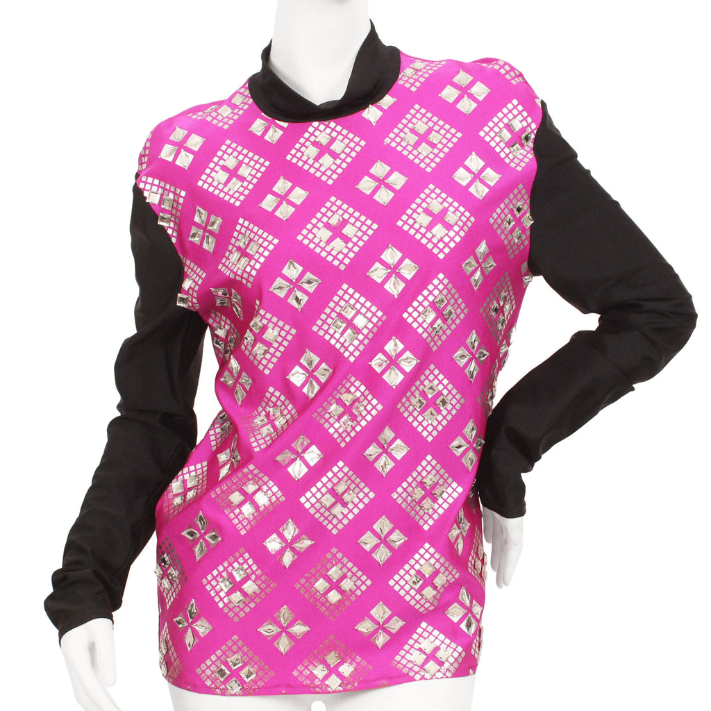 Fuschia shirt with black long-sleeves, black mock-neck, and a silver, graphic print with mirrored embellishments.