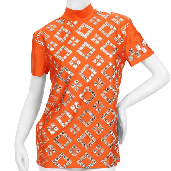 Orange, short-sleeve, mock-neck shirt with a silver, graphic print with mirrored embellishments.