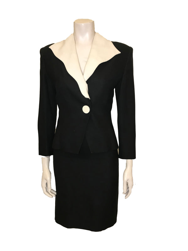 black, two-piece suit with skirt. Jacket has white collar and white front button. Skirt is knee-length and straight.
