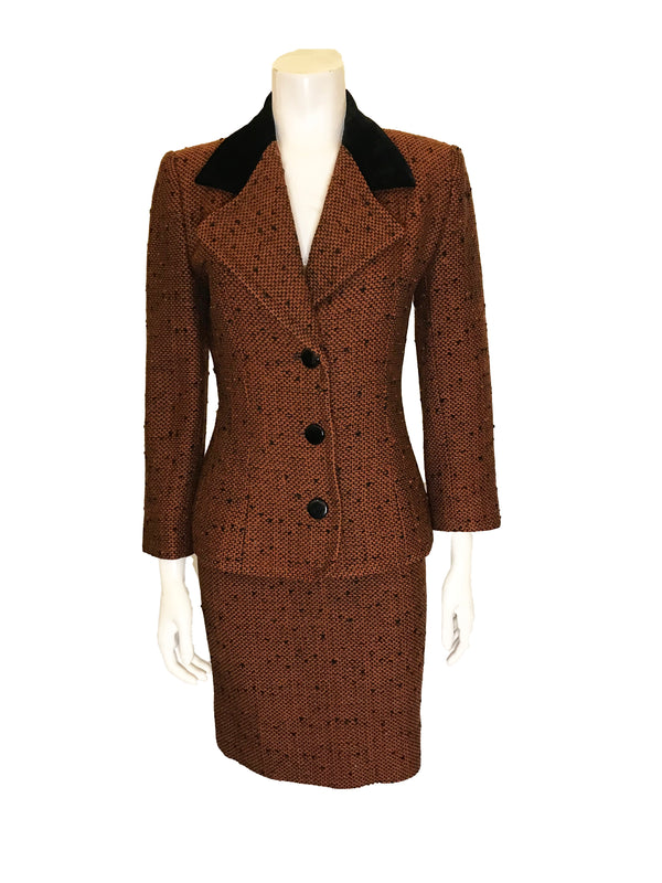 Front view on mannequin Two piece suit with skirt in burnt orange tweed wool with metallic thread. Jacket is hip length with three quarter sleeves and three button closure. Skirt is straight and knee length