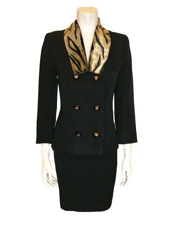 black two-piece suit with skirt. Jacket has faux fur, animal-print collar and double-breasted, pearlized buttons. Skirt is straight and knee-length.