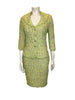 Full length front view of mannequin wearing a St John Couture lime green tweed skirt suit with four silver rhinestone buttons up the jacket front.