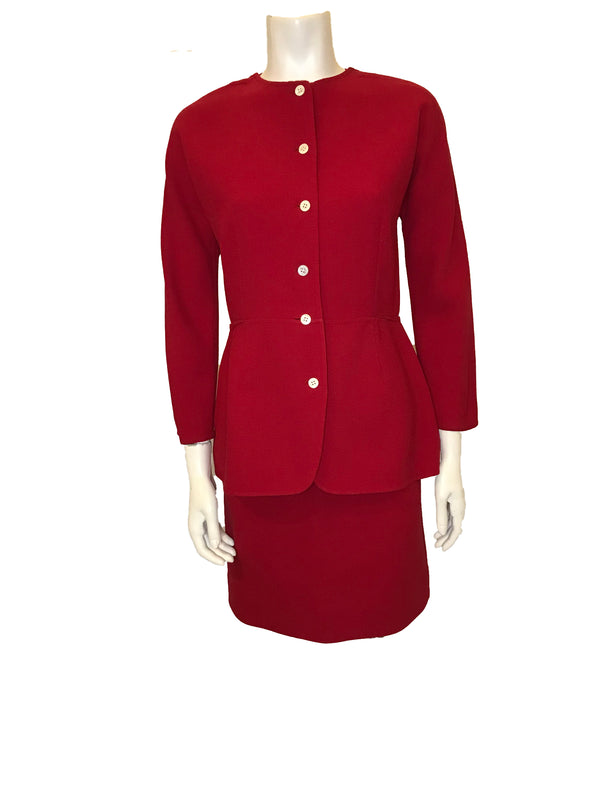 Red, two-piece skirt-suit. Jacket is hip length and has three quarter sleeves and pearlescent buttons. The skirt is straight and knee length.