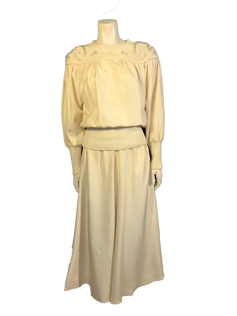 Creme, silk, two-piece set. Long-sleeve top with knit yoke and swirls of cording. Below-the-knee length skirt.