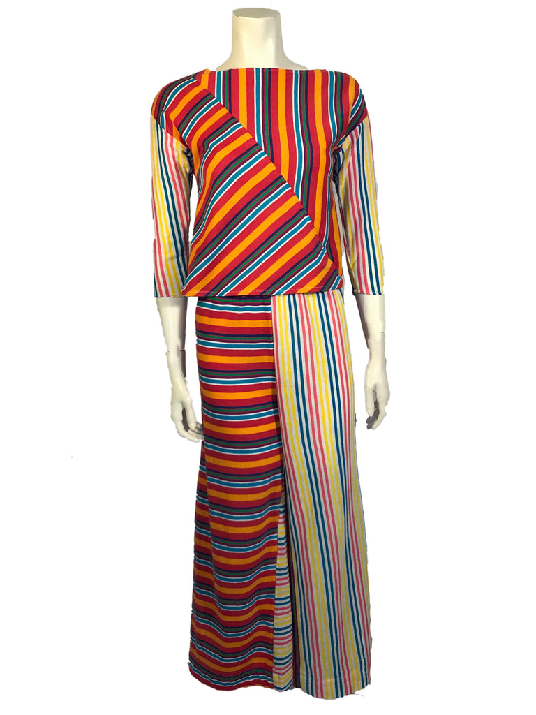 Asymmetrical, multicolor, striped, three-piece set. Three-quarter-sleeve shirt with vertical and diagonal stripes. Wide-leg pants with vertical and horizontal striped legs. Coordinating striped bonnet.