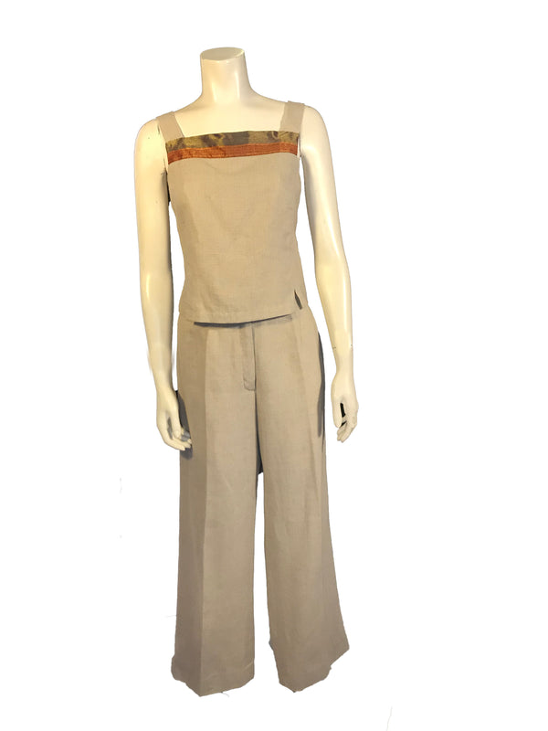 Light beige, linen, two-piece set. Sleeveless, square-neck top with orange, red, and purple metallic ribbon at the neck, and buttons down the back. High-waisted, wide-leg pants.