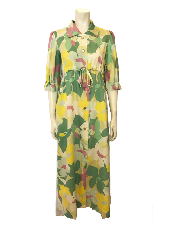 ( Front Veiw) A maxi button up robe in a pastel floral print, featuring a straight collar, voluminous mid length sleeves, and a drawstring at the front below the bustline.