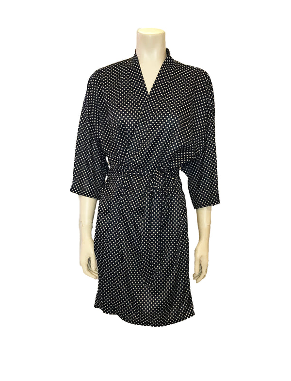 ( Front View) A knee length navy blue polka dot robe with kimono style sleeves, a sash belt, and an interior tie to keep the neckline secure.