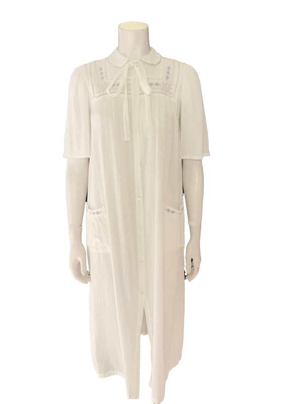 (Front View) Semi sheer white cotton gauze short sleeve housecoat with floral embroidery, a high neck with a tie, pockets, and button front closure.