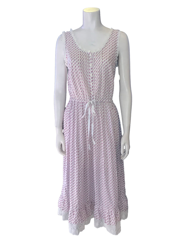 (front view) White cotton and purple floral print sleeveless Dress with a drawstring waist, round neck, and white lace trim.