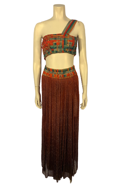 Front view of a two piece set from the Santa Fe Opera production of Salome! Woven ribbon one shoulder crop top and coordinating wine colored maxi.