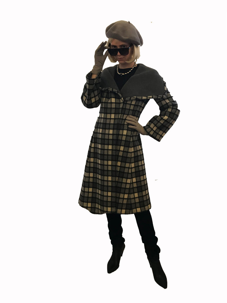 Model wearing grey plaid coat styled with a grey beret, black suede thigh high boots,  and grey suede gloves