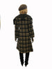 Back view of model wearing grey plaid knee length coat with  dramatic grey lapel draping over shoulders.
