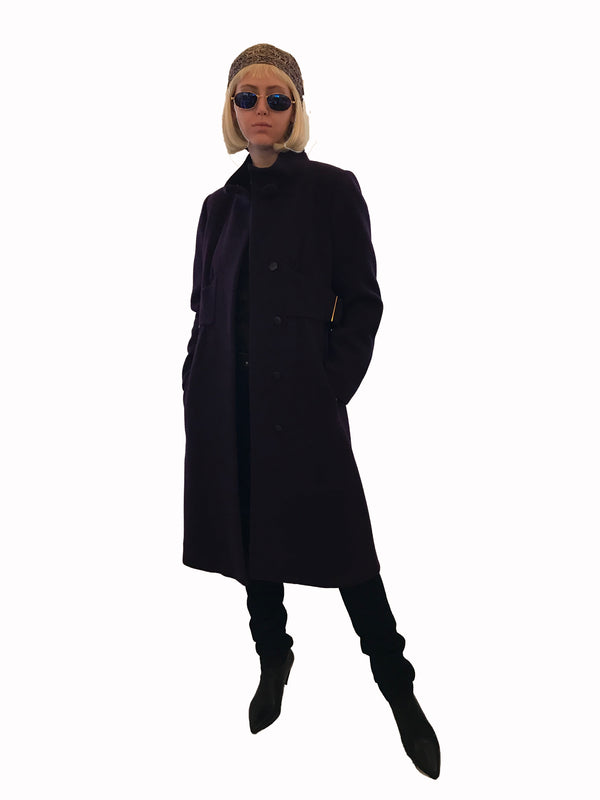 Full front view of female model wearing a purple Pauline Trigere coat styled with a head scarf, sunglasses, and black boots