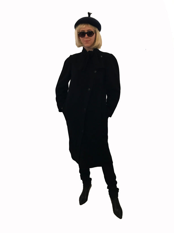 Black wool coat with high neckline that ties. Asymmetrical buttons across front.