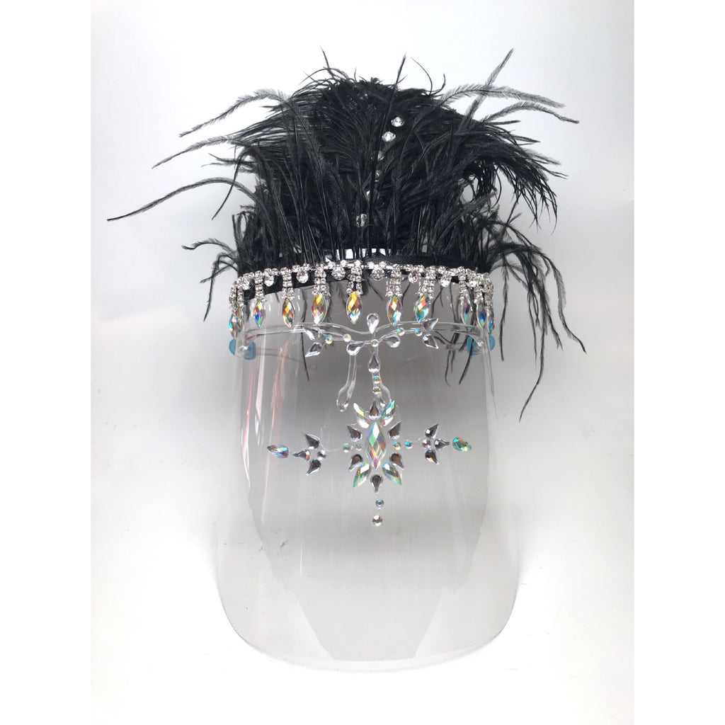 An embellished face shield with rhinestones and black feathers at the top