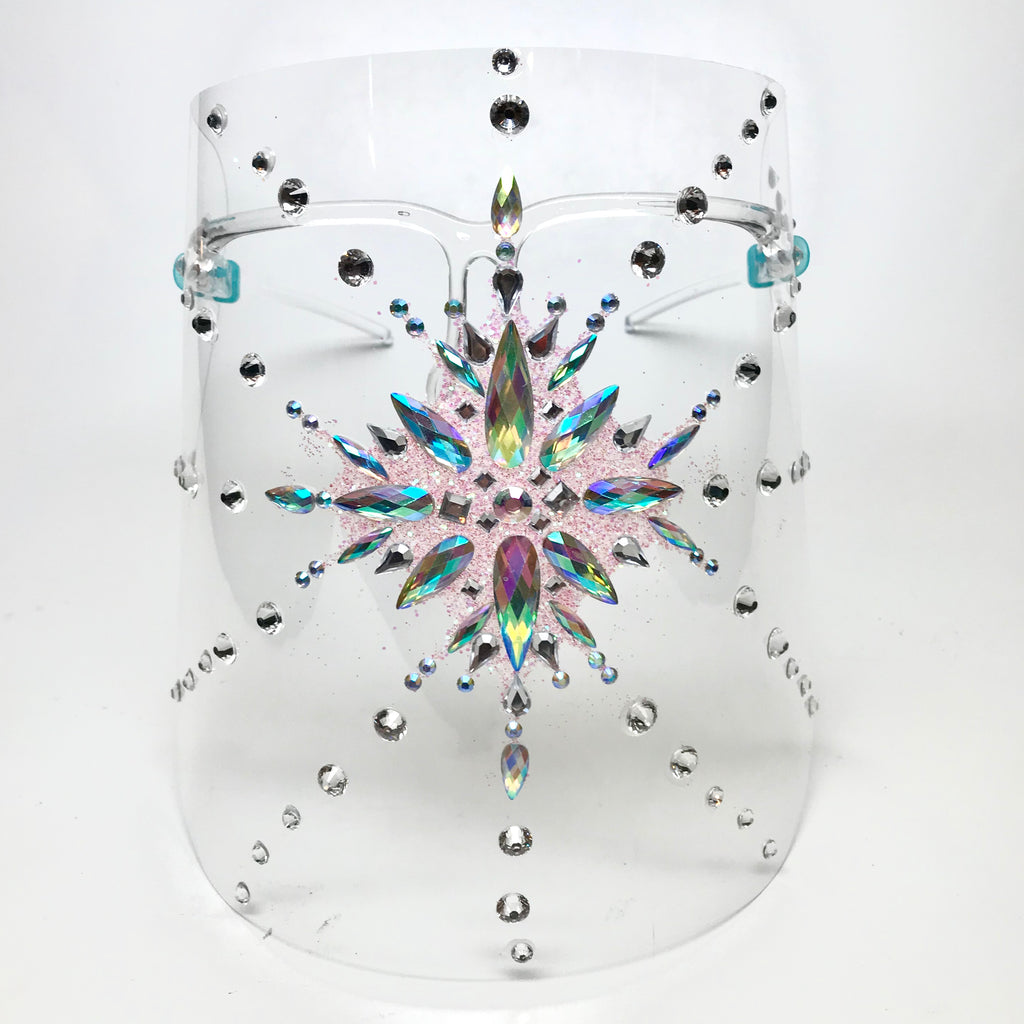 Clear plastic shield with opalescent rhinestone starburst at center with clear crystals and pink glitter . Shield has arms that rest on ears when worn.