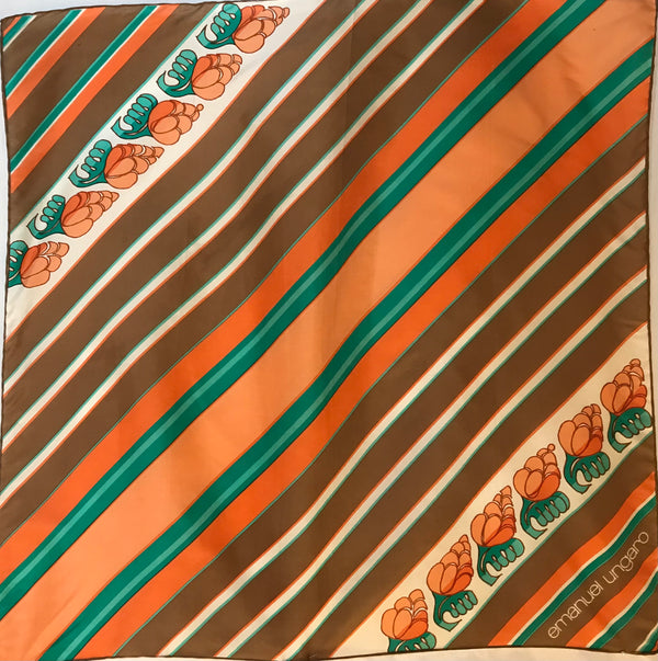 A silk scarf by Emanuel Ungaro featuring diagonal stripes in peach, brown, creme, and green with two stripes of peach flowers. The designer's logo is printed along a diagonal line near the lower righthand corner.