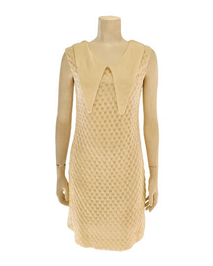 Front view of a mannequin wearing a white knit mini dress with a pointed collar