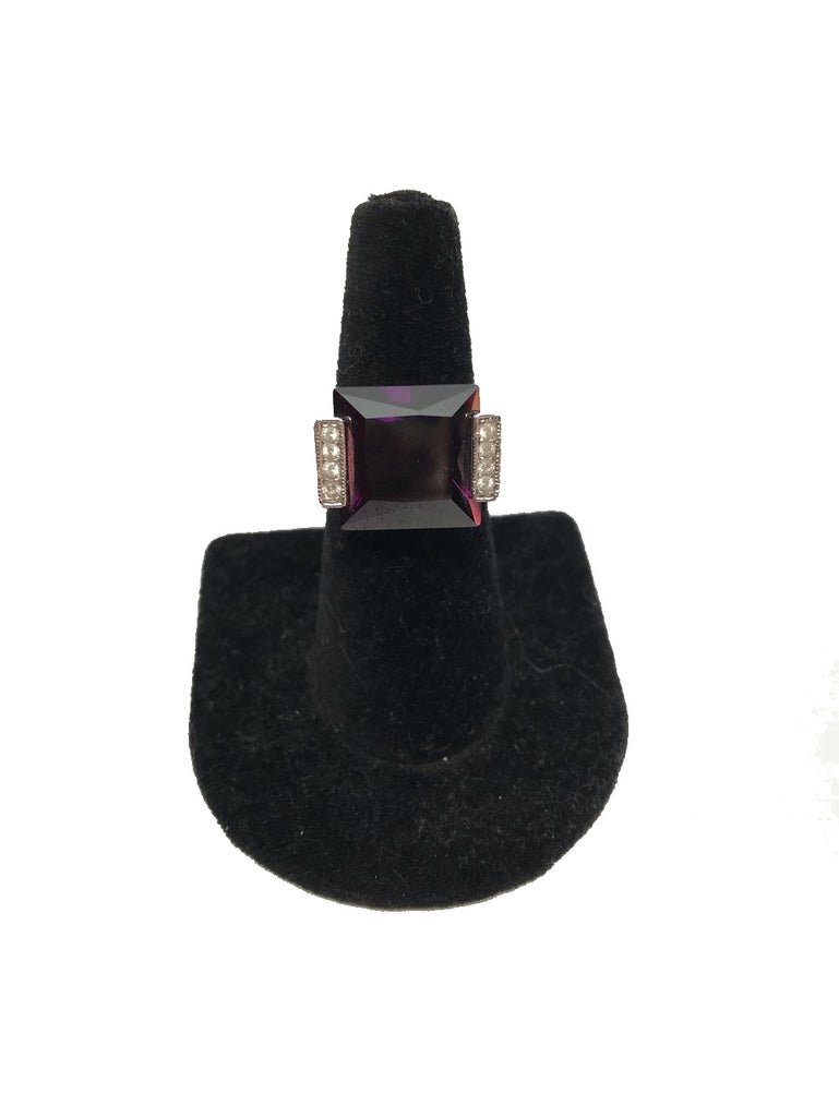 Front view of finger display with a sterling silver and amethyst zircon cocktail ring.