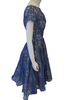 Side view of a periwinkle lace dress with short sleeves, a circle skirt, and a large creme bow
