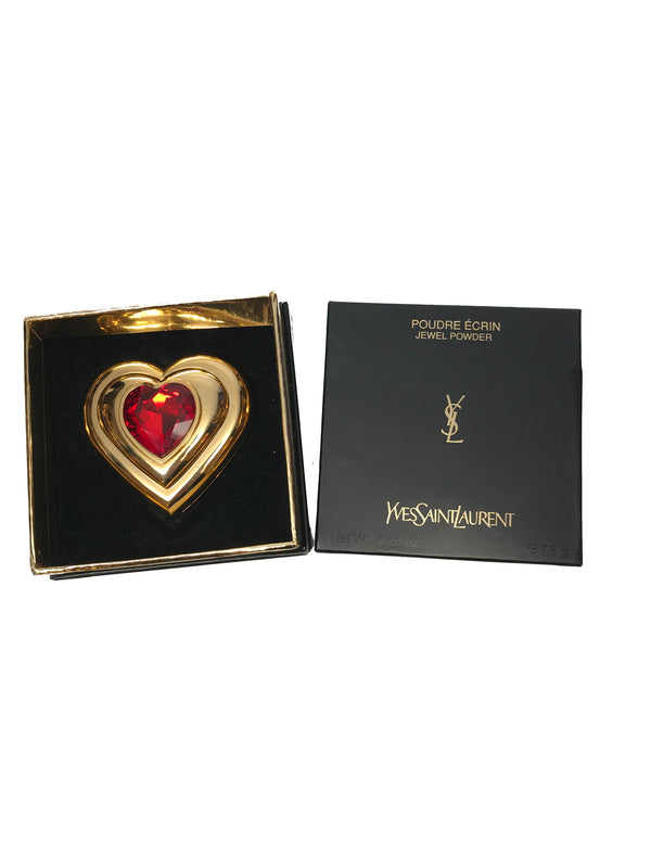 Front view of Yves Saint Laurent gold Heart shaped makeup compact with large red jewel placed in its original packaging.