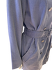 Side closeup of a mannequin in a denim double breasted trench coat with a belt, showing the side pocket.