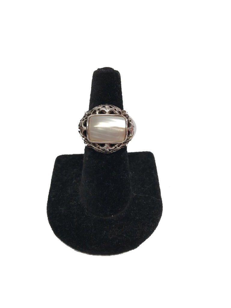 Front view of a sterling silver ring with a filigree design and a mother of pearl rectangular stone at the center.