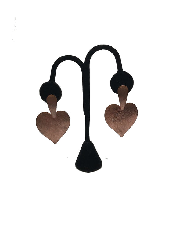 Front view of brushed copper heart shaped earrings on an earring stand