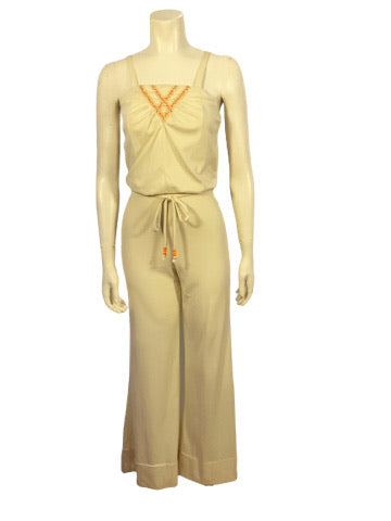 creme  polyester jumpsuit with wide leg, spaghetti strap top, floral ribbon trim at top and matching belt