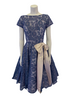 Front view of a periwinkle lace dress with short sleeves, a circle skirt, and a large creme bow