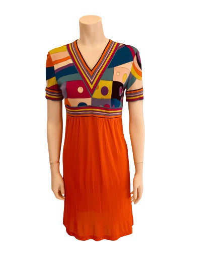 Item Sold Out. Front view of a mannequin wearing an Emilio Pucci Dress w/ a printed short sleeve upper and a solid orange skirt.