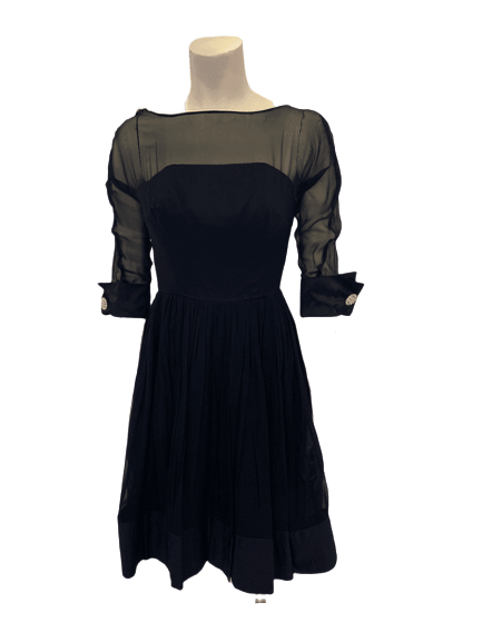 Front view of a 1950s cocktail dress with a sheer top, fittted waist, and circle skirt