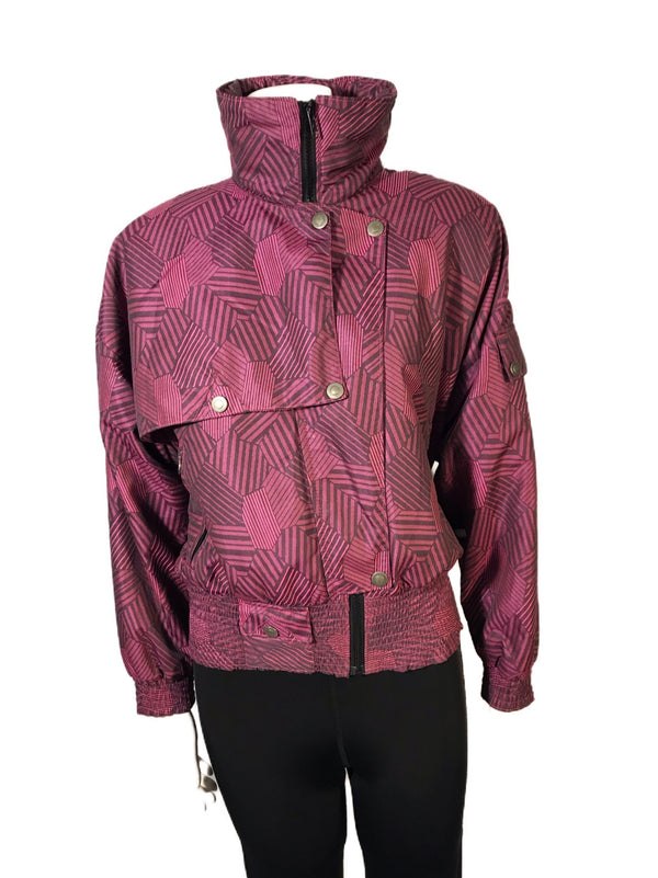 Magenta and black abstract patterned ski jacket. Asymmetrical snap front and high zip up neck.  Banded bottom