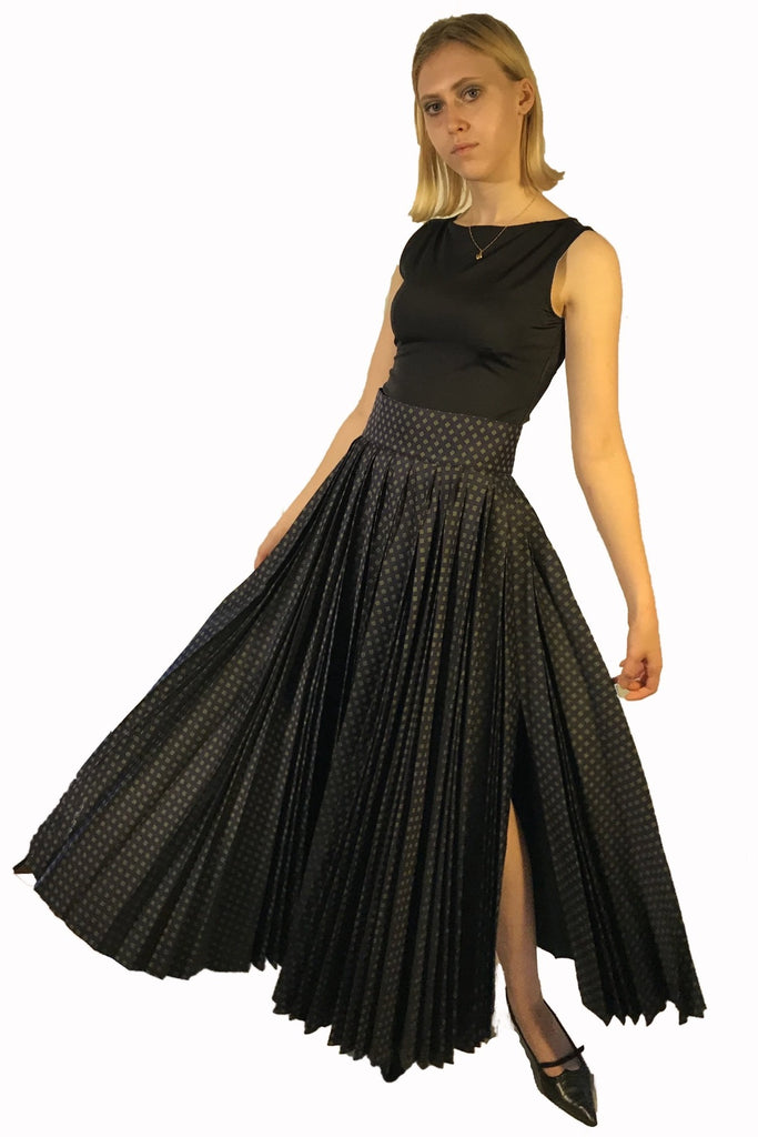 Long, high waisted full pleated skirt with side slit. Pattern is navy blue with green and white accents.