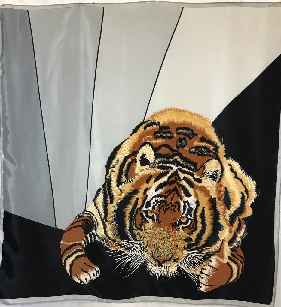 A large scarf featuring a black, grey, and white color-block background with a realistic illustration of a tiger in the foreground.