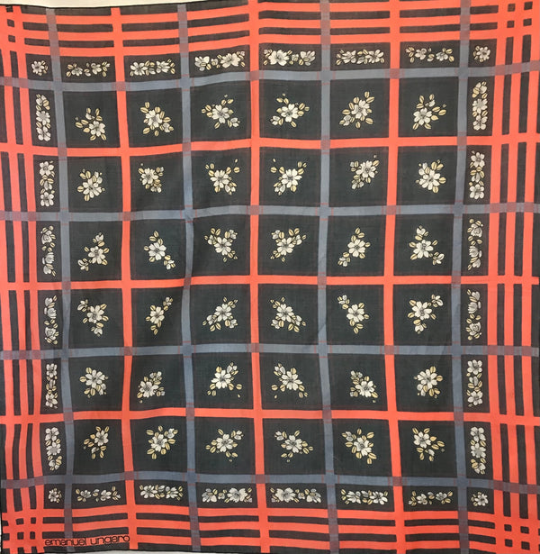 Emanuel Ungaro scarf with a black background and oversize windowpane plaid motif in coral and grey-blue. In the squares of the plaid, there are small clusters of blue and white flowers.