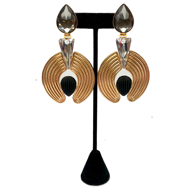 Gold-tone, clip-on earrings. Teardrop rhinestone connects to texturized gold-tone pieces with inverted teardrop piece at the center.