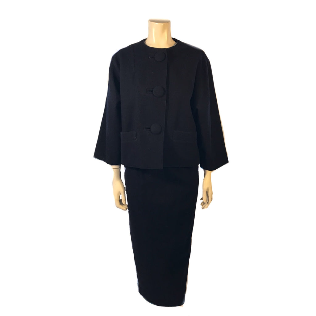 Navy, wool, two-piece skirt suit. Jacket is boxy and hip length with three buttons. Skirt is straight and midcalf length