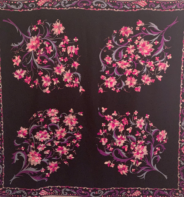 Black silk square scarf  with four floral  patterns in pink, purple, blue. and white. Border is a paisley pattern in a matching color scheme.