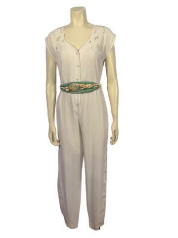 White cotton cap sleeve jumpsuit with gathered waist, tapered leg that buttons at ankle. top has cutouts in a floral desin. Comes with a rope and shell belt in green and creme.
