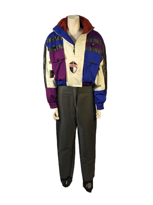 Long-sleeve ski jumpsuit in a color-block pattern of purple, blue, cream, and grey. Zip-up front with 2 large pockets on chest.