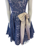 Closeup front view of a periwinkle lace dress with short sleeves, a circle skirt, and a large creme bow