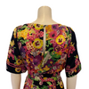 Silk, short-sleeve dress with a waist-tie. Yellow, pink, and purple floral print on black base.