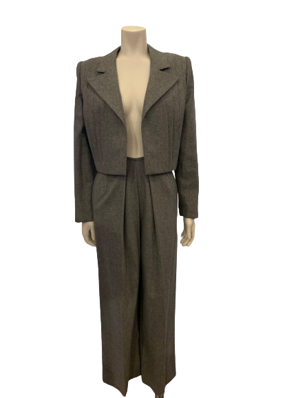 Two piece suit with pleated pants in a grey wool. Jacket has a pleated open front. Pants are full.