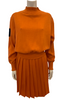 "Orange, knit, long-sleeve, mock-neck sweater with black, ""Junior Gaultier"" patch on sleeve and a matching, orange, knit, knee-length, pleated skirt."