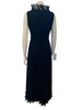Back view of mannequin in 1970s sleeveless black maxi dress with ruffles at the neck and hem