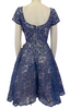 Back view of a periwinkle lace dress with short sleeves, a circle skirt, and a large creme bow