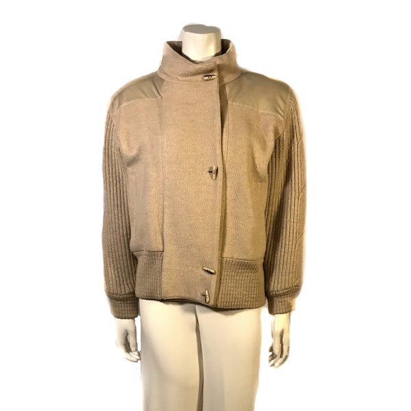 Front  view on mannequin beige wool waist length jacket with knitted wool sleeves and banded bottom. Four front buttons